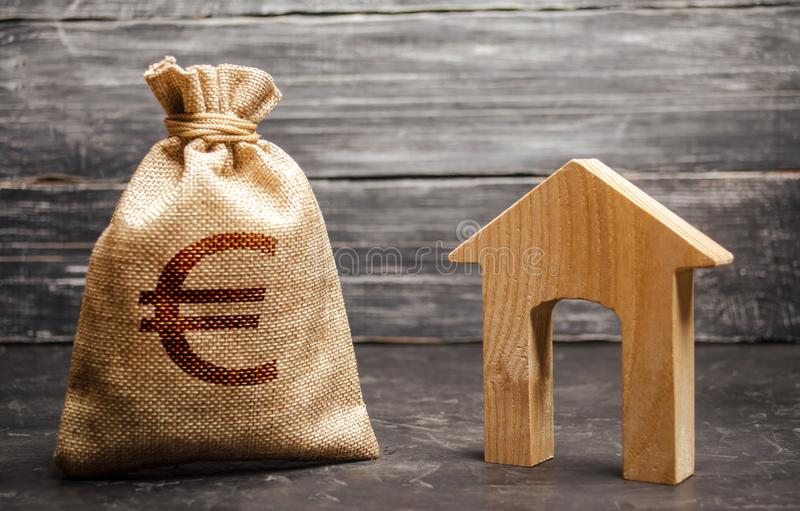 A bag with euro money and a House with a large doorway. Taxes, rental income. Building houses. rent or purchaseConcept of real royalty free stock photo