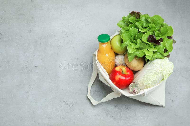 Bag with fresh vegetables, apples and bottle of juice on color background, top view. Space for text stock photography