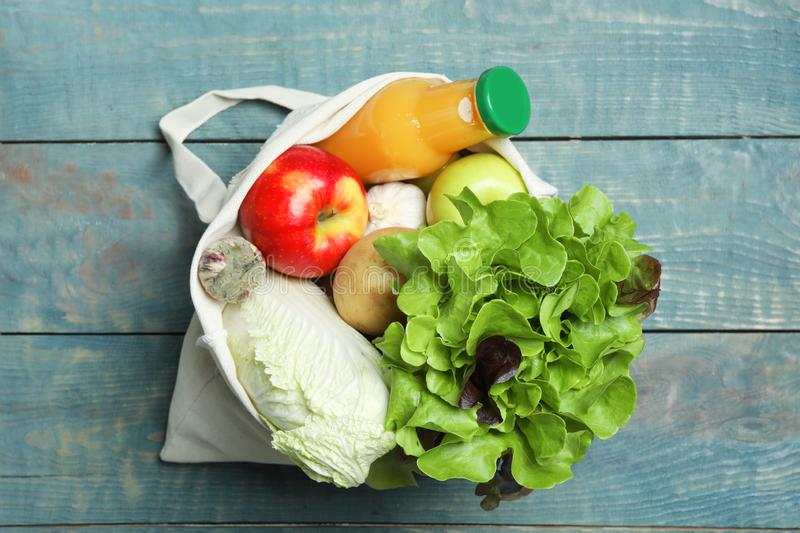 Bag with fresh vegetables, apples and bottle of juice on wooden background. Top view stock images