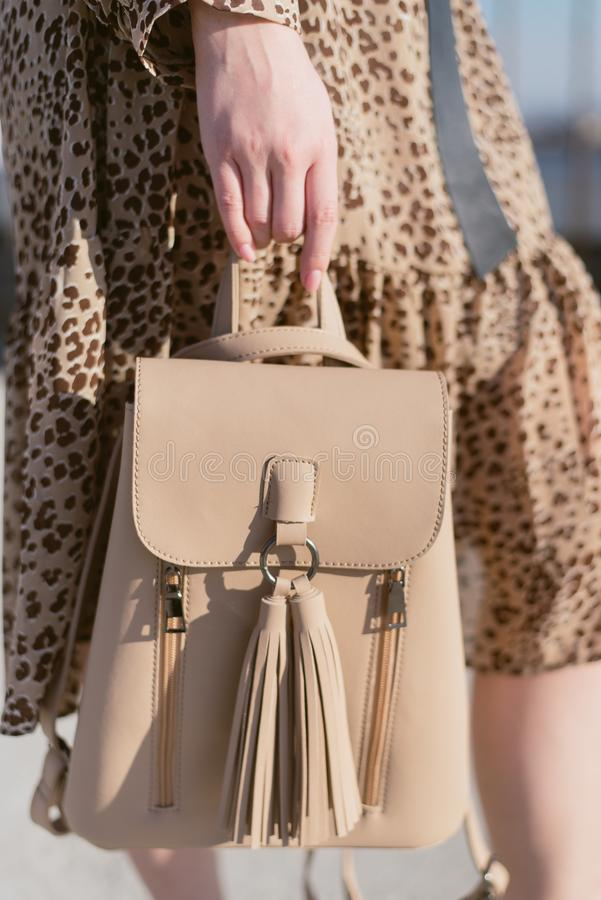 beige backpack in the hands of a girl on the street royalty free stock image
