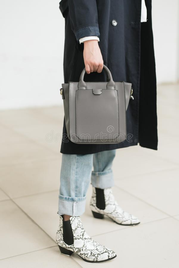 Bag in hand, blue jeans and blue raincoat royalty free stock photo
