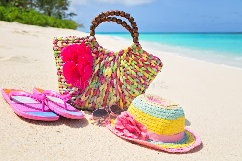 Bag, hat, flip-flops and sunglasses on sunny beach, tropical beach vacation and travel concept.  royalty free stock image