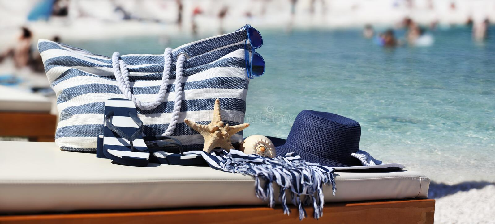 bag with hat, sandals, starfish, sea shell and towel on the beach stock images