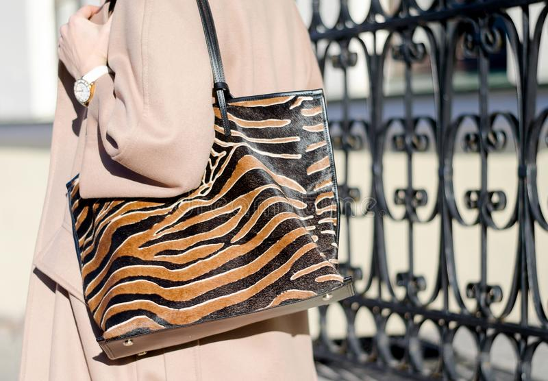 Bag in leopard print close-up. large shopping leather handbag in female hands. Woman walking in the city. Girl in a beige coat royalty free stock photos
