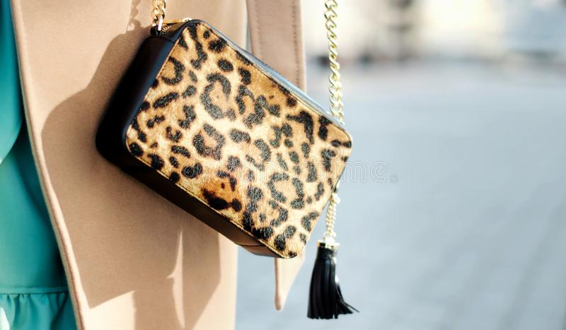 Bag in leopard print close-up. large shopping leather handbag in female hands. Woman walking in the city. Girl in a beige coat stock image