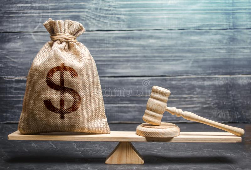 Bag of money with a dollar sign and a judge`s hammer on the scales. Concept lobbying for the adoption of a law or a norms,. Corruption. Payment of fines and royalty free stock image