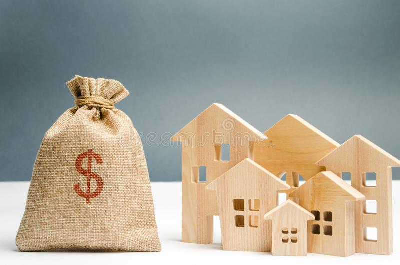 Bag with money and dollar sign and wooden houses. Financing in the country. Investing money in real estate. Saving and. Accumulation of money. Mortgage. Buying stock photos