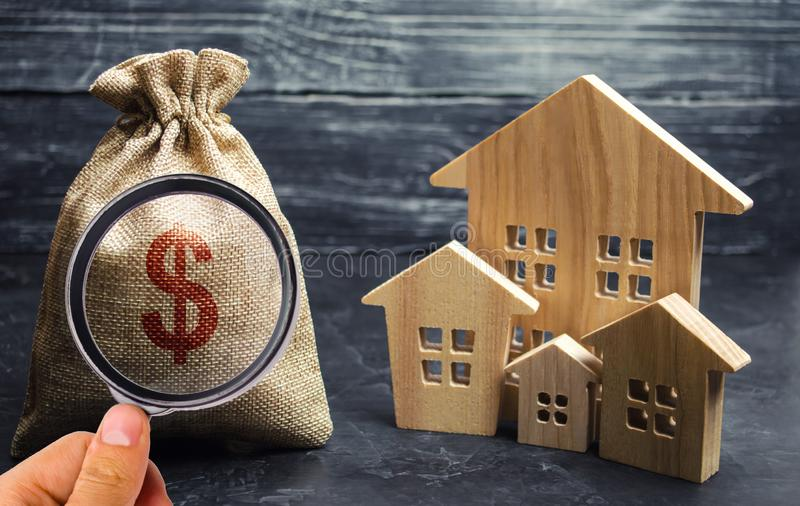 Bag with money and dollar sign and wooden houses. Financing in the country. Investing money in real estate. Saving and royalty free stock photography