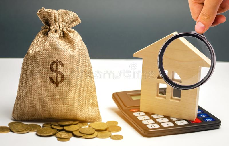 Bag with money and dollar sign and wooden houses. Financing in the country. Investing money in real estate. Saving and stock image