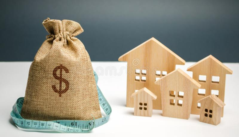 Bag with money and dollar sign and wooden houses with tape measure. Limited city budget. Investing money in real estate. Saving. And accumulation of money stock image