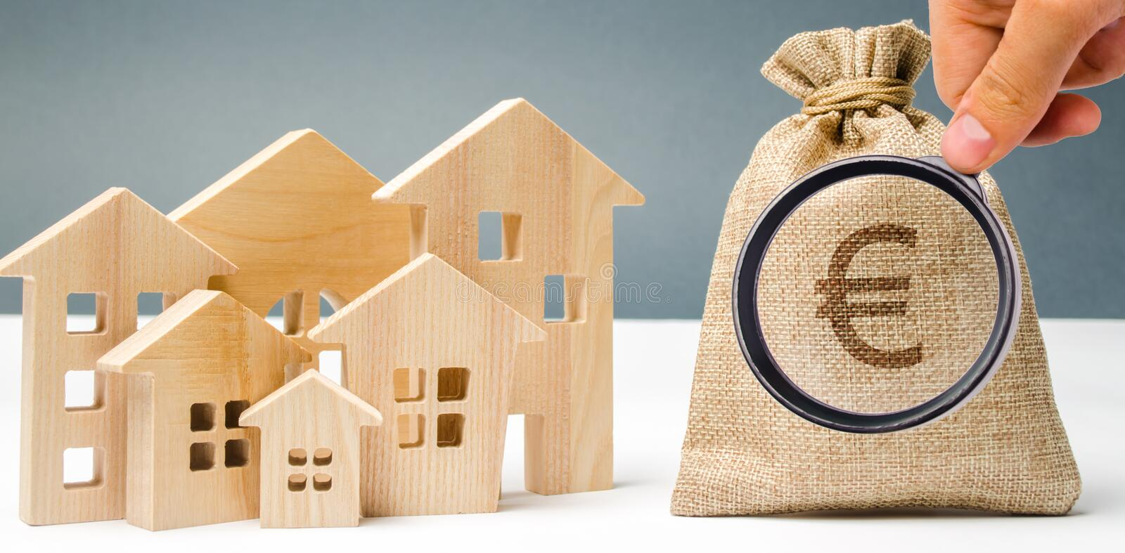 Bag with money and euro sign and wooden houses. Financing in the country. Investing money in real estate. Saving and accumulation. Of money. Mortgage. Buying a royalty free stock image