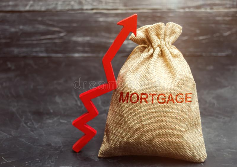 A bag with money and the inscription Mortgage and up arrow. Raising mortgage rates and tax. The increase in interest charges. Loan. For housing, apartment and royalty free stock images