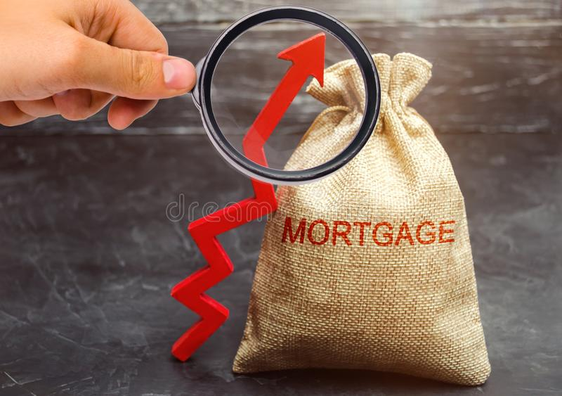 A bag with money and the inscription Mortgage and up arrow. Raising mortgage rates and tax. The increase in interest charges. Loan. For housing, apartment and royalty free stock photography