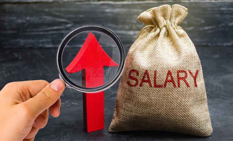 A bag with money and the inscription Salary and up arrow. increase of salary, wage rates. promotion, career growth. raising the royalty free stock images