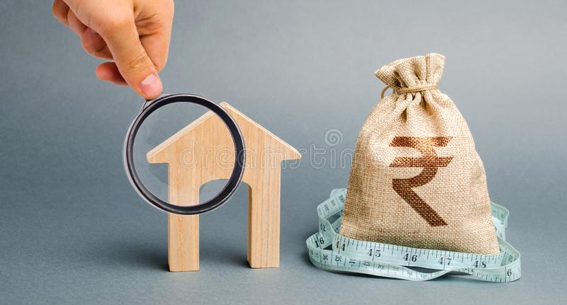 Bag with money and tape measure with a wooden houses. The concept of a limited real estate budget. Market crisis. Bankruptcy. Low stock images