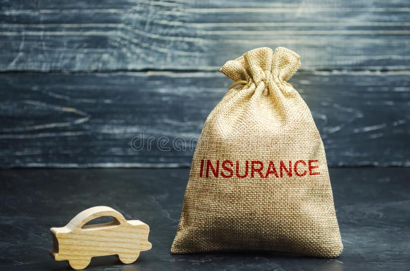 A bag with money and the word Insurance and a car. Car protection. Auto insurance. Repair and maintenance of vehicles. A wooden stock photo