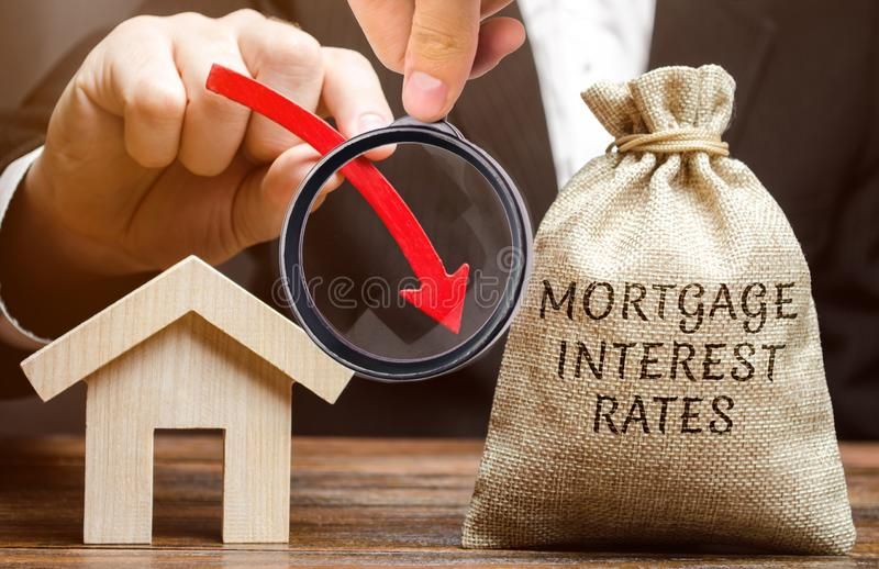 Bag with the money and the word Mortgage interest rates and arrow down and house. Low interest in mortgages. Reducing interest. Payments for mortgages. The fall royalty free stock images