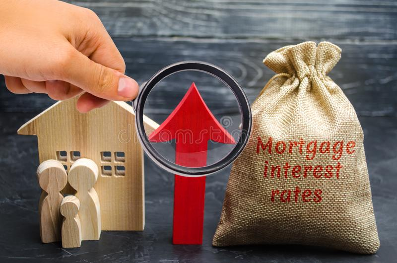 Bag with the money and the word Mortgage interest rates and up arrow with family and home. Raising mortgage rates and tax. The. Increase in interest charges royalty free stock image