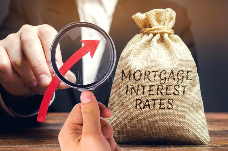 Bag with the money and the word Mortgage interest rates and up arrow in male hands. Raising mortgage rates and tax. The increase. In interest charges. Loan for royalty free stock photos