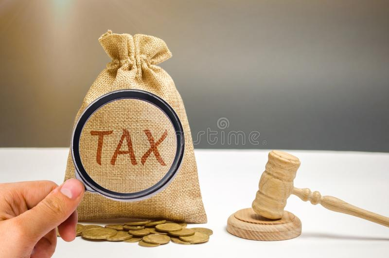 Bag of money and the word Tax and hammer of the judge. Law concept. Court and judgment. Justice and legality. Legislators, public. Administration. Property tax royalty free stock image