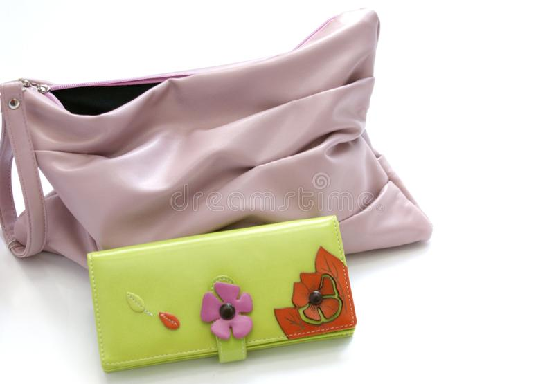 Bag and purse. Pink small handbag and green big purse on a white background royalty free stock photo