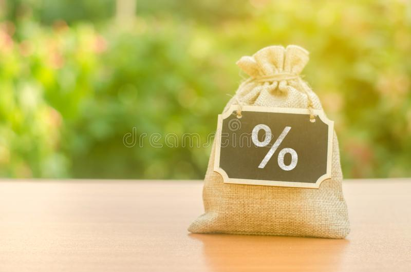 Bag with a sign and a percent symbol on the background of nature. Concept of deposit or credit. Taxes Interest rate. Bag with a sign and a percent symbol on the stock photo