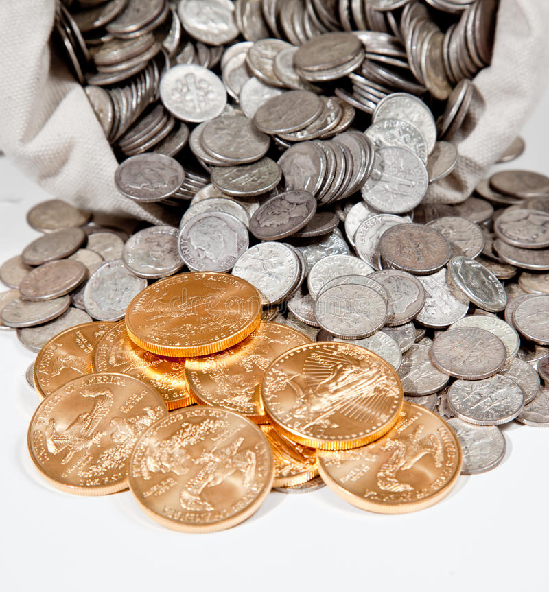 Bag of silver and gold coins. Linen bag of old pure silver coins used to invest in silver as a commodity with a selection of Golden Eagle gold coins stock photos