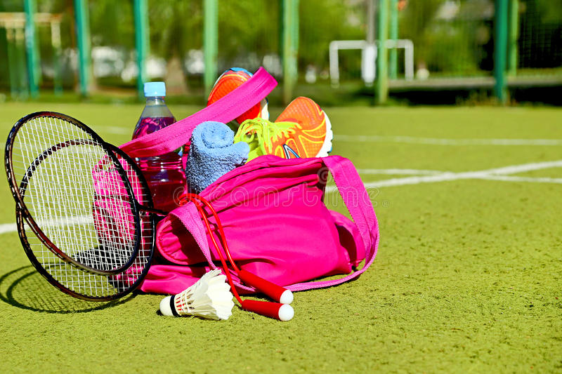 Bag with sports equipment on the sports courts. Bag with sports equipment on the sports courts background. Badminton ball (shuttlecock), racket, rope, sneakers stock photography