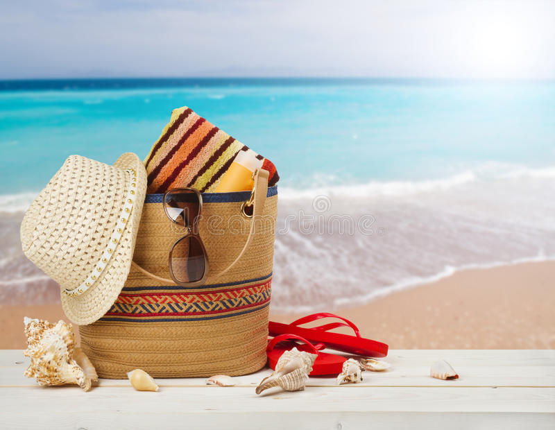 Bag, sunglasses, hat and flip flops on sea beach background royalty free stock photos