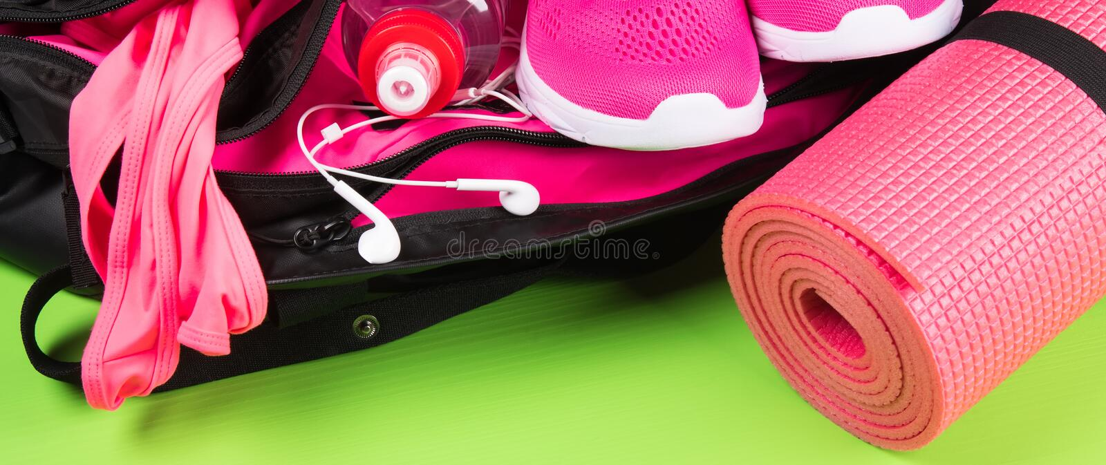 Bag with things for fitness on the green floor, long photo stock photos