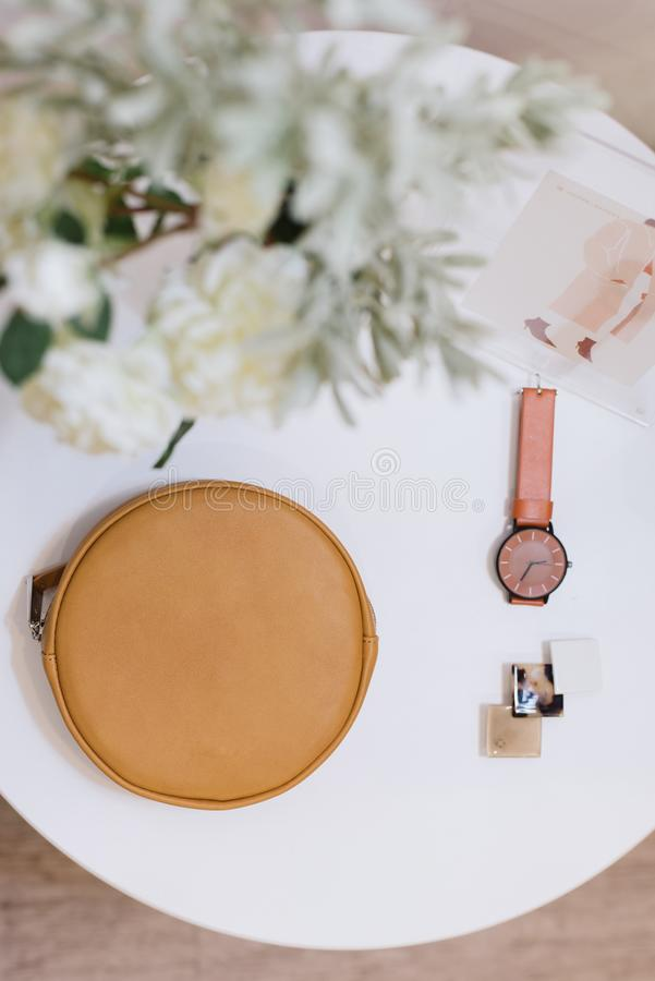 Bag, watch and barrette lie on a white table royalty free stock photography
