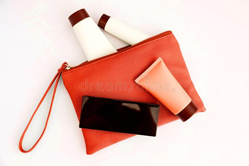 Bag with woman`s cosmetics. Women`s secrets. Deodorant, lipstick, eau de toilette, perfume, different care creams. Red bottles with cosmetics royalty free stock photos