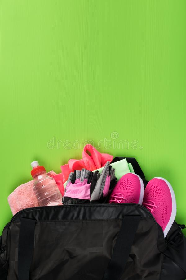 In the bag are womens sports things for fitness on a green background. In the bag are women`s sports things for fitness on a green background royalty free stock photo