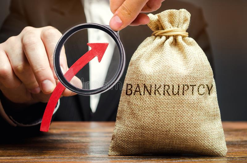 A bag with the word Bankruptcy and an up arrow in the hands of a businessman. The high level of bankruptcy in the country. The royalty free stock images