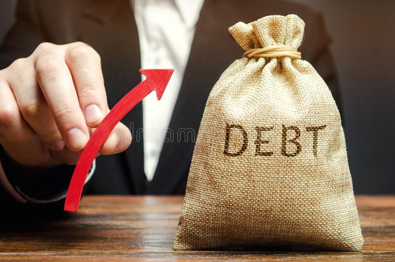 A bag with the word Debt and an up arrow in the hands of a businessman. Receivables. The growth of debts for utilities and payment. Of salaries. High level stock image