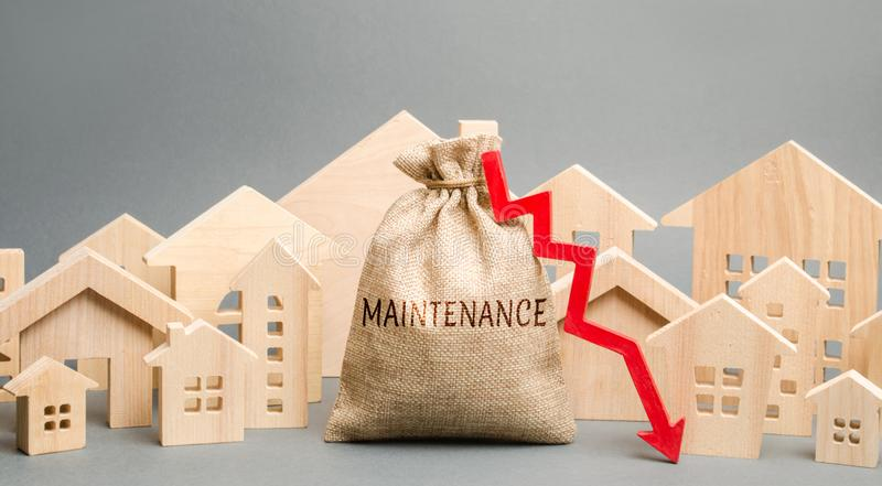 A bag with the word Maintenance, wooden houses and down arrow. Reducing the cost of maintaining the house. Improving energy. Efficiency and environmental stock image