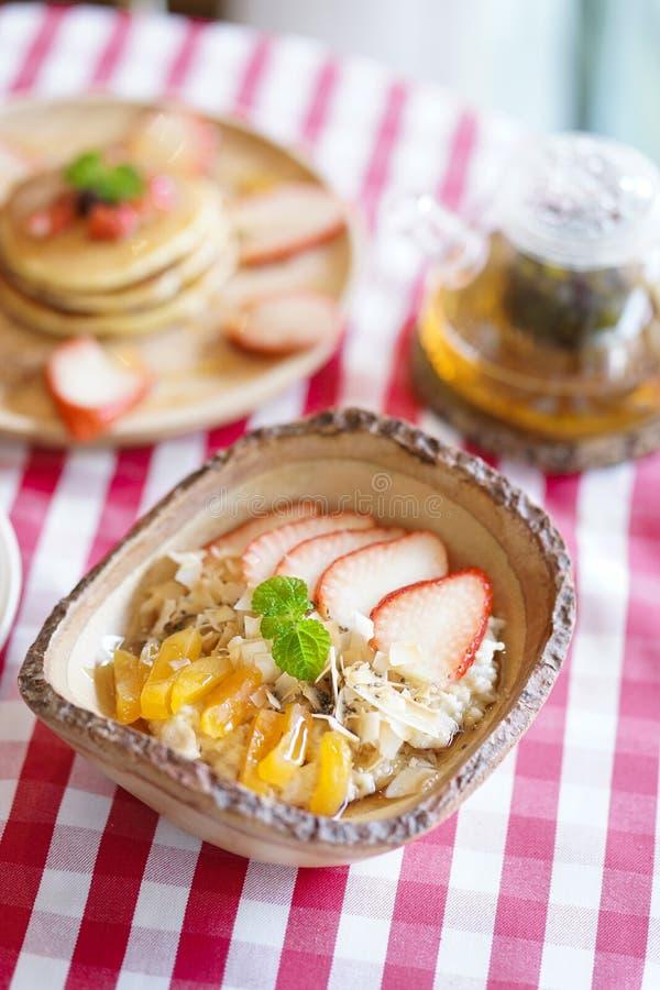 Bagaço Farinha de aveia servida com frutos frescos, tais como pêssegos e morangos para o café da manhã imagens de stock