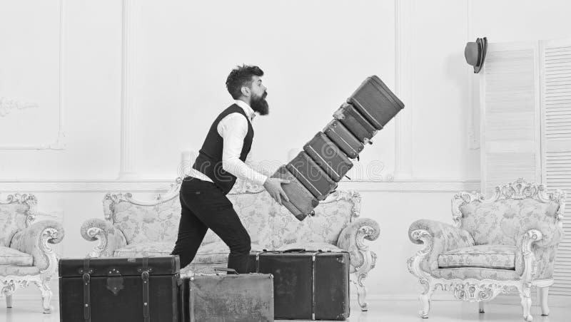 Bagażowego ubezpieczenia pojęcie Mężczyzna z brodą i wąsy w klasycznym kostiumu dostarcza bagaż, luksusowy biały wnętrze zdjęcie stock