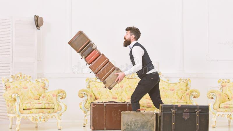Bagażowego ubezpieczenia pojęcie Mężczyzna z brodą i wąsy w klasycznym kostiumu dostarcza bagaż, luksusowy biały wnętrze fotografia stock