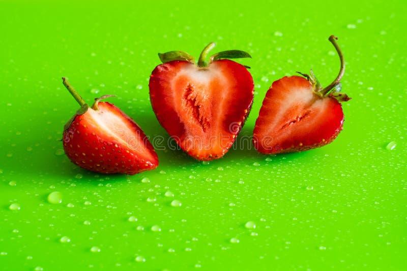Baga madura doce vermelha da morango no fundo verde do resíduo metálico com gotas da água fotografia de stock royalty free