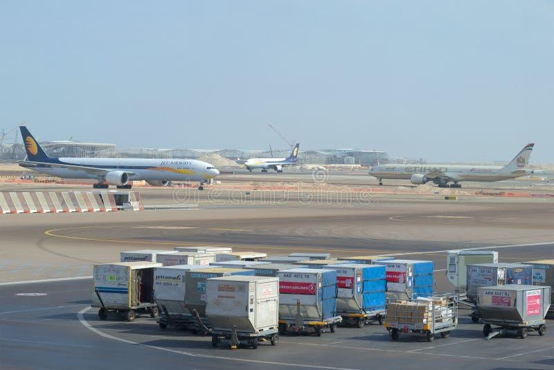 Bagage carts i bakgrunden flygfältet av den internationella flygplatsen av Abu Dhabi royaltyfri bild
