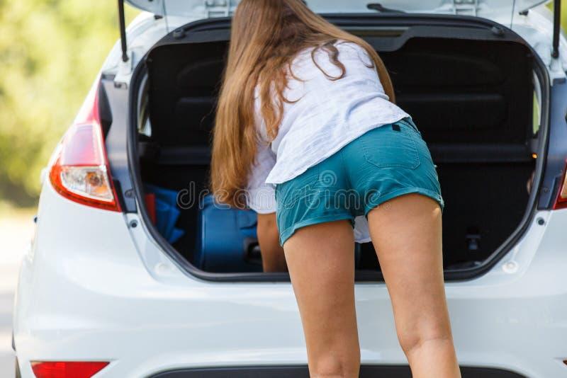 Bagage de chargement de jeune femme dans le tronc de la voiture images stock