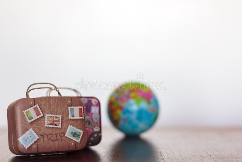 Bagage de voyage de cru et globe de la terre sur une table avec l'espace blanc de fond et de copie concept de course photo libre de droits
