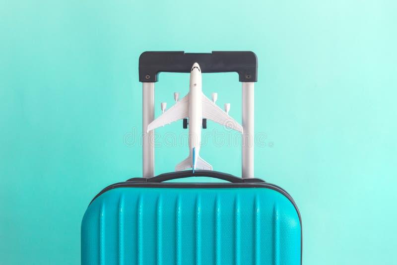 Bagage met klein vliegtuig op groen achtergrond minimalistic vakantieconcept royalty-vrije stock foto's