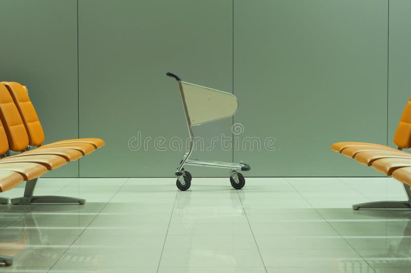 Bagagekar tussen de rijen van lege stoelen stock fotografie