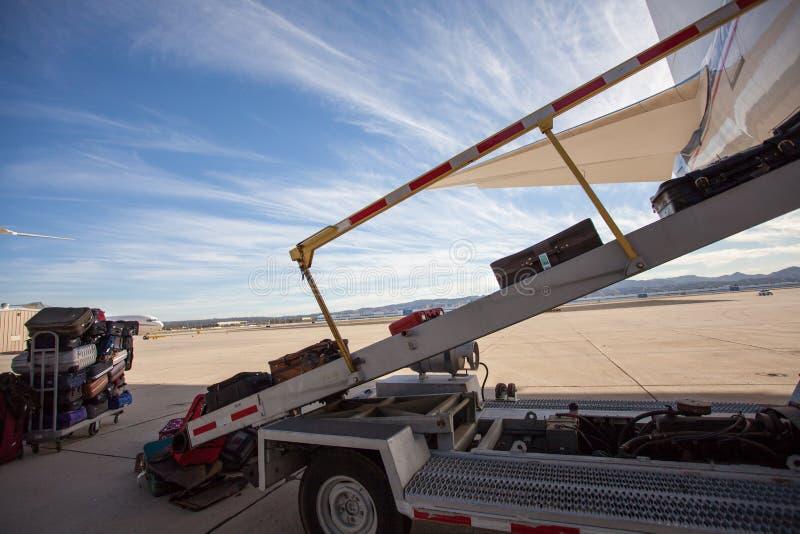 A bagagem está sendo carregada em um avião comercial em um alcatrão Dia bonito no aeroporto com nuvens dramáticas fotografia de stock royalty free