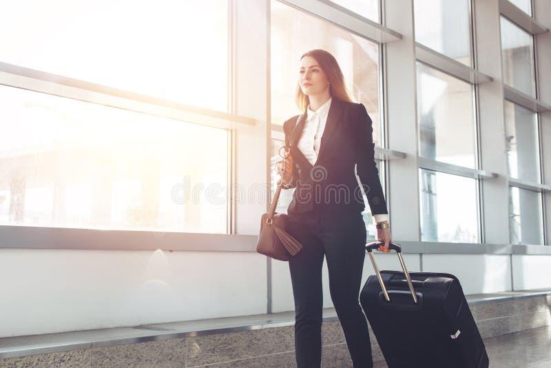 Bagagem levando consideravelmente de sorriso do aeromoço fêmea que vai ao avião no aeroporto fotografia de stock