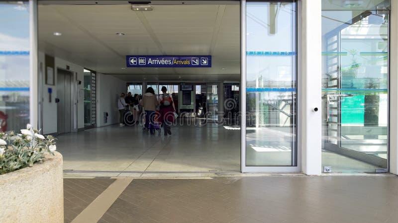 Bagagem levando dos povos ao longo do terminal, da chegada e da partida de aeroporto do turista imagens de stock