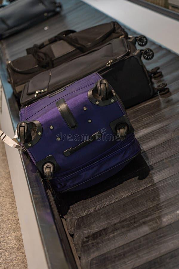 Bagagens de passageiros na correia transportadora no terminal de chegada do aeroporto imagem de stock royalty free