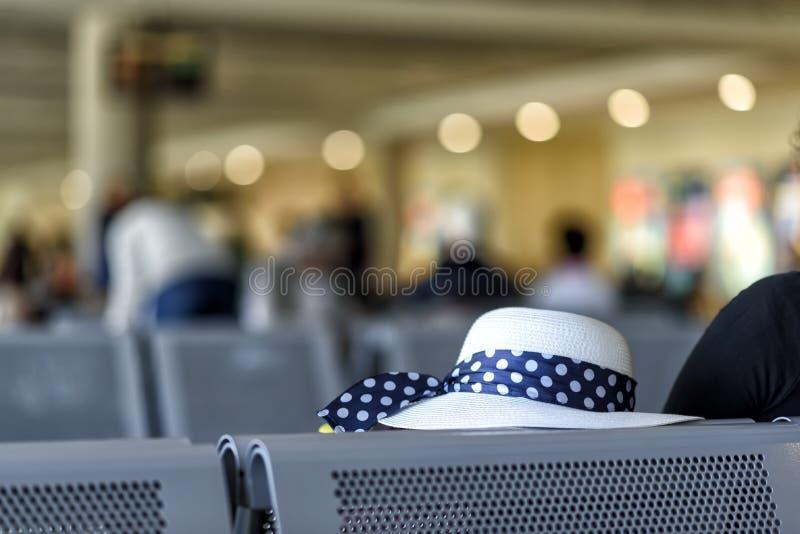Bagaglio di cabina e un cappello all'aeroporto fotografia stock libera da diritti